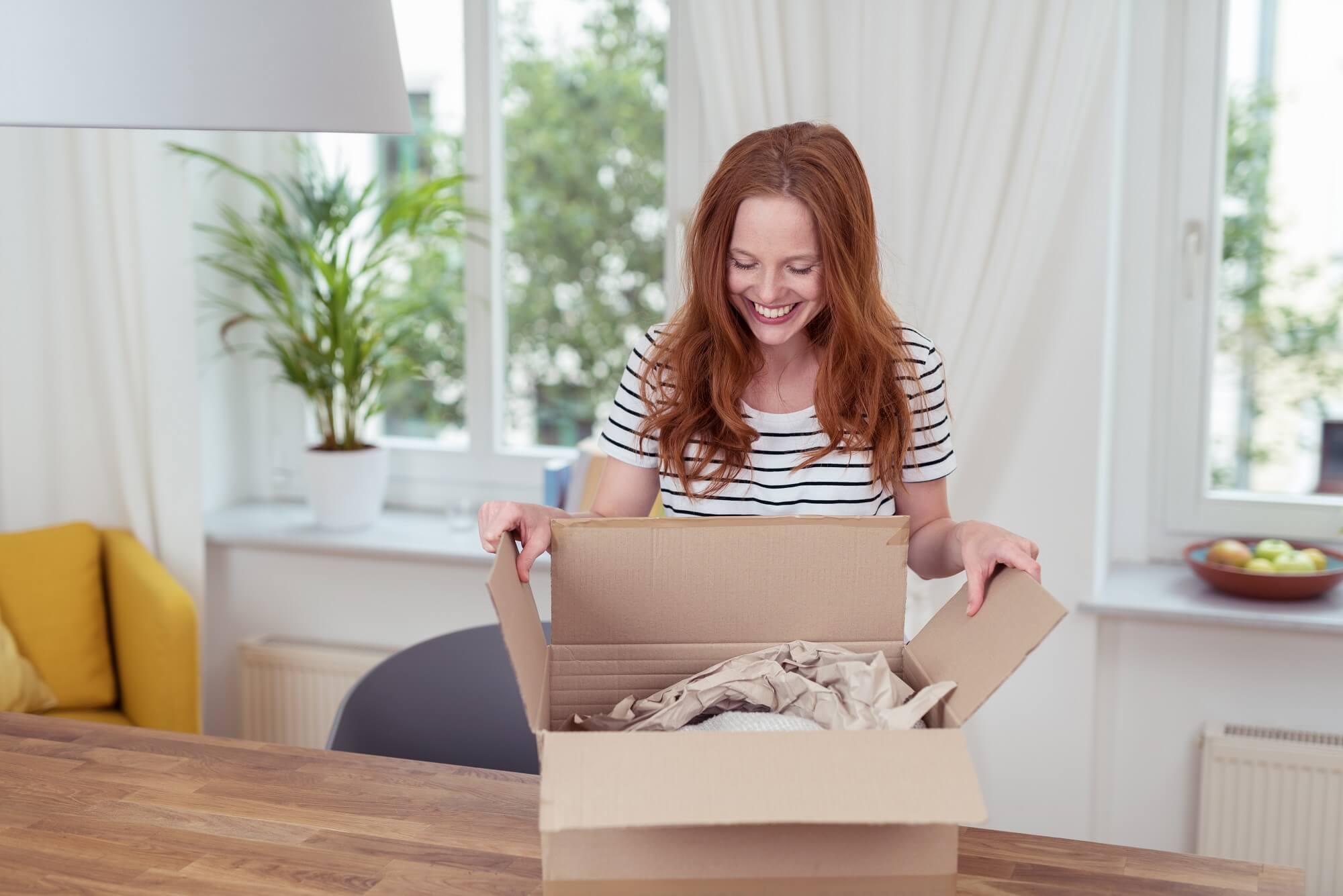 kobieta pakuje przesyłkę w domu